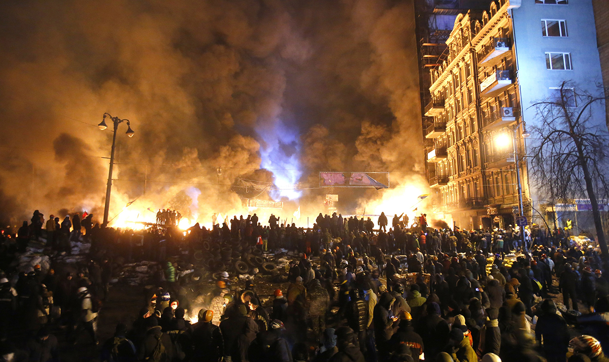 "FILE - In this file photo taken on Saturday, Jan. 25, 2014, smoke and fireballs rise during clashes between protesters and police in central Kiev, Ukraine. The ""Heavenly Hundred"" is what Ukrainians in Kiev call those who died during months of anti-government protests in 2013-14. The grisliest day was a year ago Friday _ Feb. 20, 2014 _ when sniper fire tore through crowds on the capital's main square, killing more than 50 people. A year later, so much has changed. Russia has annexed Ukraine's Crimean Peninsula, Ukraine has a new president and government, and the country is embroiled in a war in the east with Russia-backed separatists that has killed over 5,600 people and forced a million to flee. (AP Photo/Sergei Grits, File)"